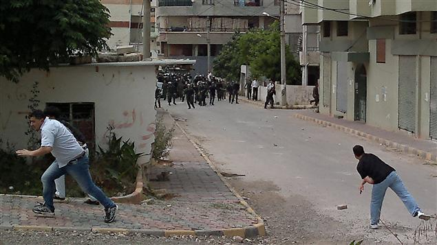 Cette photo fournie par un pigiste montre des manifestants lançant des pierres en direction des forces de sécurité à Banias.