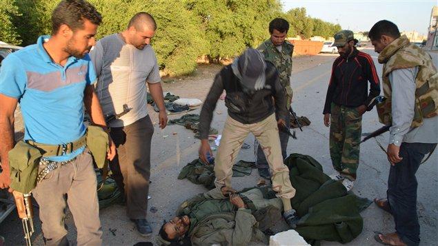 Des rebelles libyens regardent le corp d'un soldat fidèle à Mouammar Kadhafi dans le village d'al-Rayayna