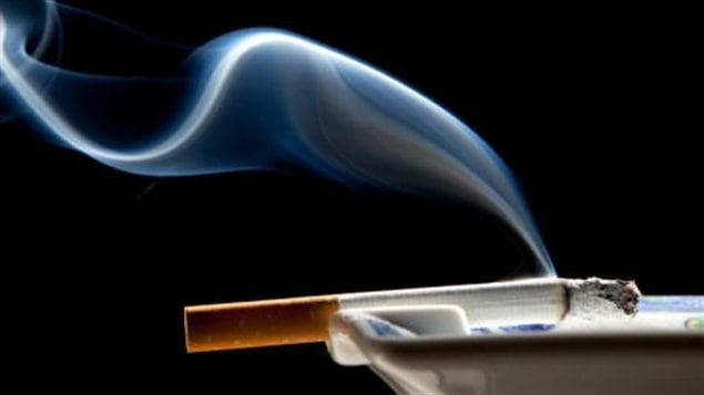 Une cigarette brûle dans un cendrier