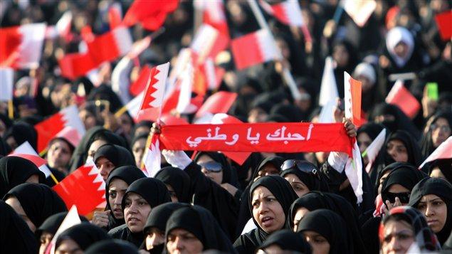 Une femme porte une banderole disant « J'aime mon pays » lors d'une manifestation organisée par le groupe d'opposition Al-Wefaq à Sitra, à Bahreïn.