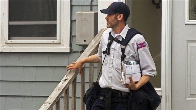 Un facteur effectue la livraison du courrier à Halifax, le 30 mai.