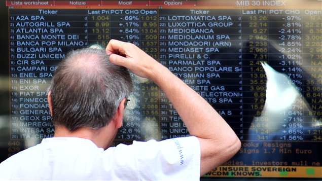 Un homme regarde les cotes à la Bourse de Milan lundi.