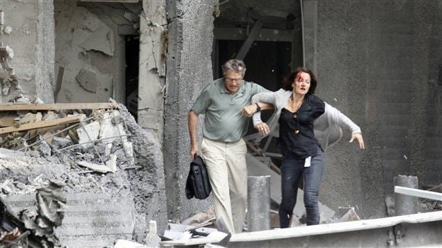 Un homme aidant une blessée à quitter un bâtiment touché par l'explosion