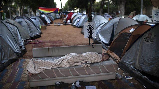 Un Israélien dort dans un campement de tentes érigé à Tel-Aviv pour protester contre la hausse des prix du logement.