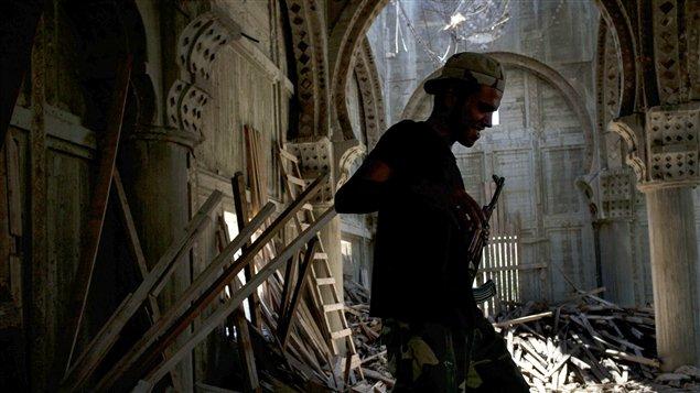 Un rebelle libyen marche dans les décombres d'une mosquée, à Sabrata, qui a servi d'abri durant les bombardements du régime de Mouammar Kadhafi.