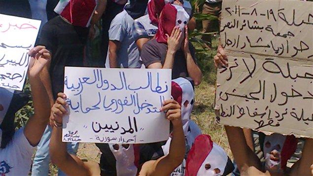 Opposants syriens avec leurs pancartes.