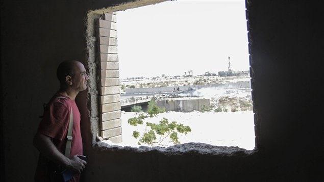 Un rebelle libyen observe les combats qui se déroulent près du complexe de Bab Al-Aziziya.
