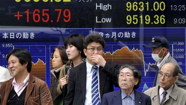 Des Japonais devant un tableau électronique de la Bourse de Tokyo.
