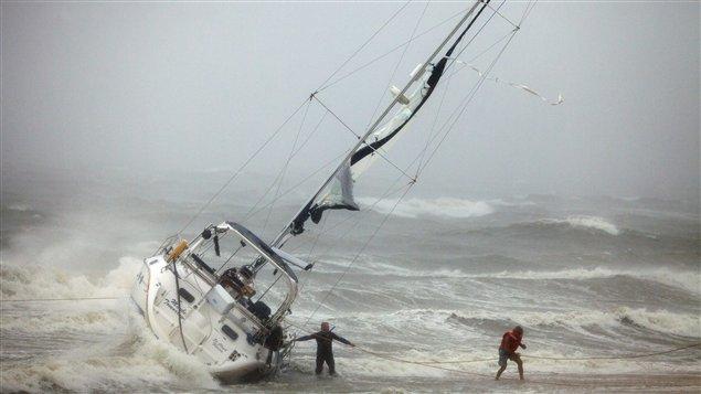 Deux personnes secourues d'un bateau à voile tentent de se rendre sur la plage à Norfolk, en Virginie