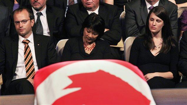 Olivia Chow entourée de Mike et Sarah Layton devant le cercueil de Jack Layton.