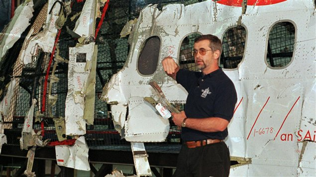 L'enquêteur du Bureau de la sécurité des transports Don Enns montre aux journalistes des débris du vol 111, en mai 1999.