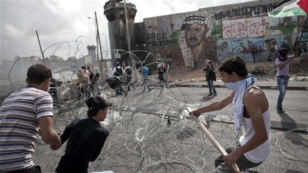 De jeunes Palestiniens tentent d'enlever des fils barbelés près d'un point de contrôle entre Jérusalem et Ramallah, lors d'escarmouches avec des soldats israéliens.