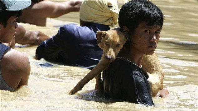 Des Philippins évacuent la ville Calumpit, inondée.