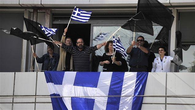 Des employés du ministère grec des Finances manifestent devant les bureaux du ministère à Athènes, le 14 octobre.