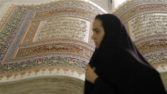 Une femme devant une sculpture représentant le Coran en Iran.