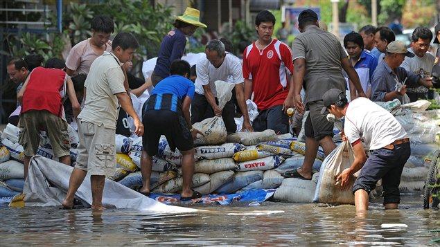 Habitants de Bangkok remplissant des sacs de sable.