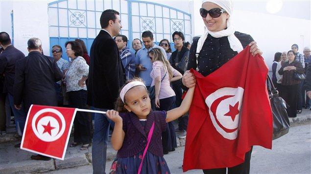 Une petite fille accompagne sa mère dans un bureau de vote à Tunis, le 23 octobre 2011.