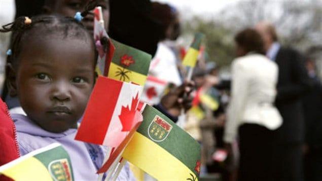 Une jeune réfugiée du Soudan brandissant des drapeaux du Canada et de la Saskatchewan à Régina, en 2006.