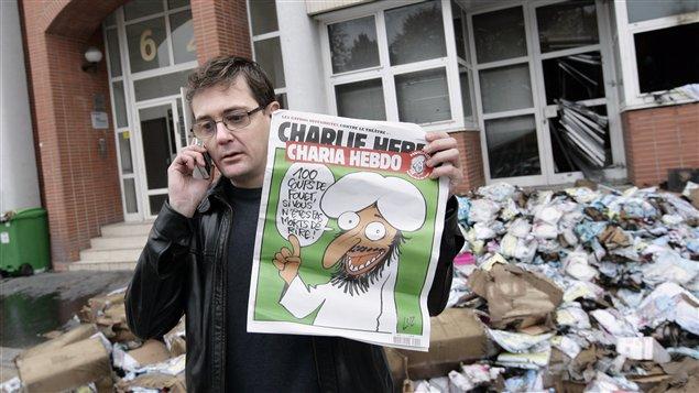 Le directeur de la publication de Charlie Hebdo montre le numéro spécial sur le printemps arabe devant les locaux incendiés de l'hebdomadaire.