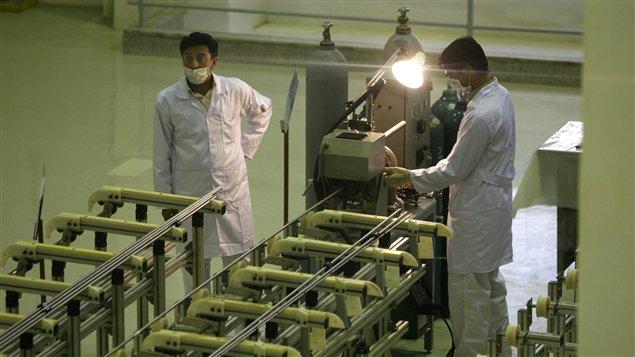 Des Iraniens travaillent dans une usine de production d'uranium.