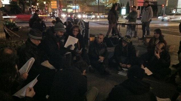 Des occupants du square Victoria discutaient d'un document expliquant les raisons de leur indignation, mardi soir.