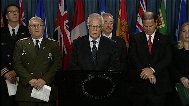 Le ministre québécois Robert Dutil (au centre) et des représentants de corps policiers et de groupes de défense du registre.