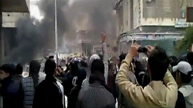 Dans les rues de Damas, des manifestants prennent en photo l'attaque d'un bureau du part Baas au pouvoir.