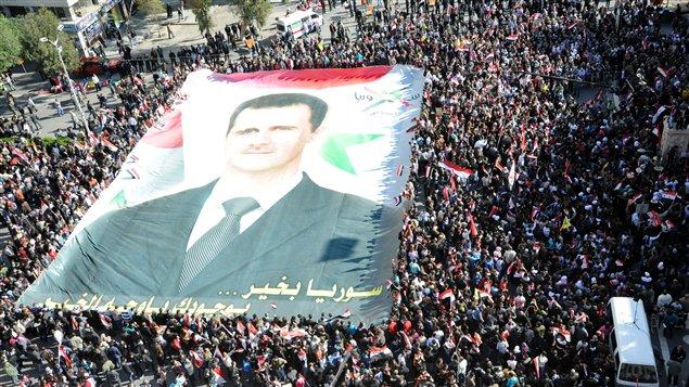 Des manifestants autour d,un portait géant de Bachar Al-Assad.