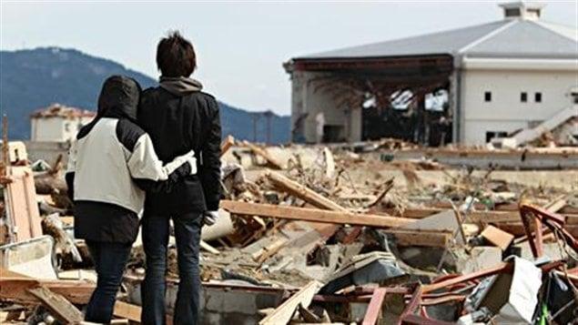Des jeunes Japonais se recueillent sur les lieux de leur village dévasté