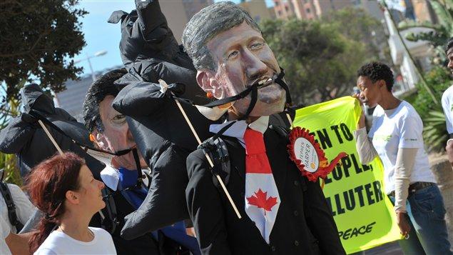Un manifestant à Durban porte un masque géant du premier ministre canadien Stephen Harper, le 5 décembre