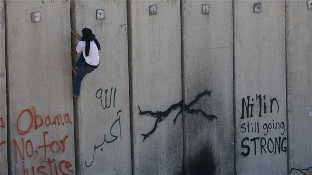 Un Palestinien escalade le mur (archives)