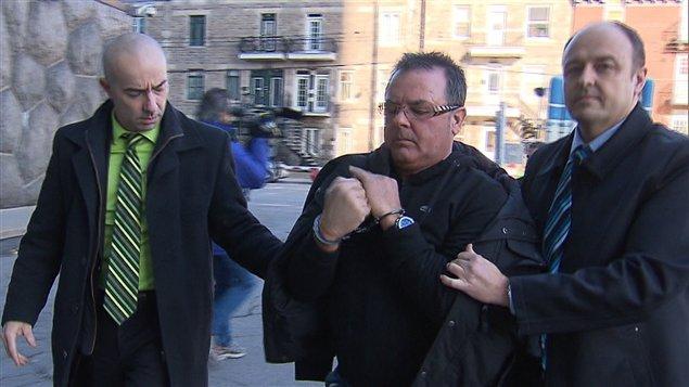 Raynald Desjardins escorté par les policiers après son arrestation.