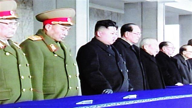 Kim Jong-un entouré de militaires et d'hommes d'État sur le balcon surplombant la vaste place Kim Il Sung.