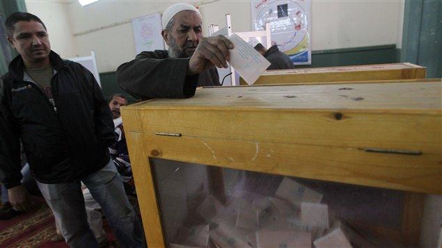 Électeur égyptien glissant son bulletin dans l'urne.