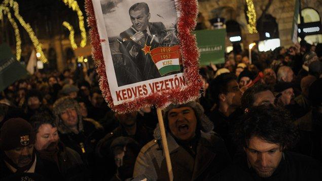 Des manifestants brandissent une pancarte représentant le premier ministre hongrois Viktor Orban en dictateur communiste, lundi, à Budapest.