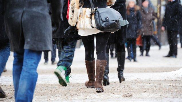 Des piétons sur une rue enneigée