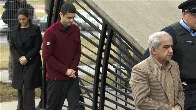 Mohammad Shafia est escorté par un policier au palais de justice de Kingston, suivi de son fils Hamed Mohammad et de sa seconde épouse, Tooba Yahya.
