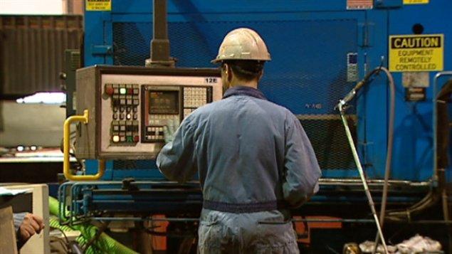 Un travailleur contrôle une machine dans une usine albertaine
