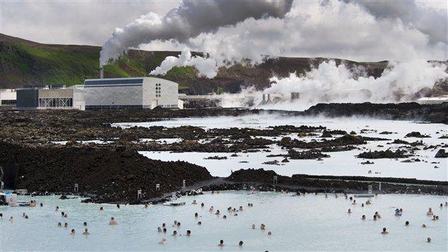 Des touristes dans le Blue Lagoon à Svartsendi à côté d'une centrale électrique.
