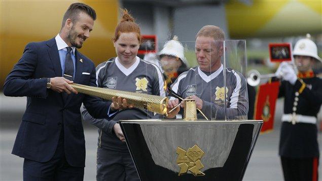 David Beckham transmet la flamme olympique à sa sortie de l'avion, à Londres.