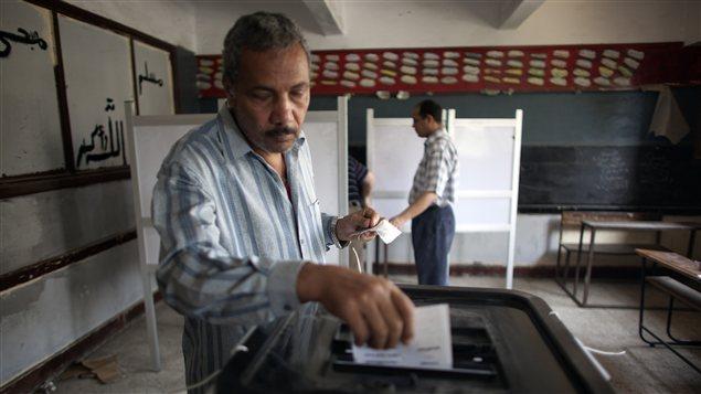 Un Égyptien vote au Caire afin de choisir le successeur du président déchu Hosni Moubarak.