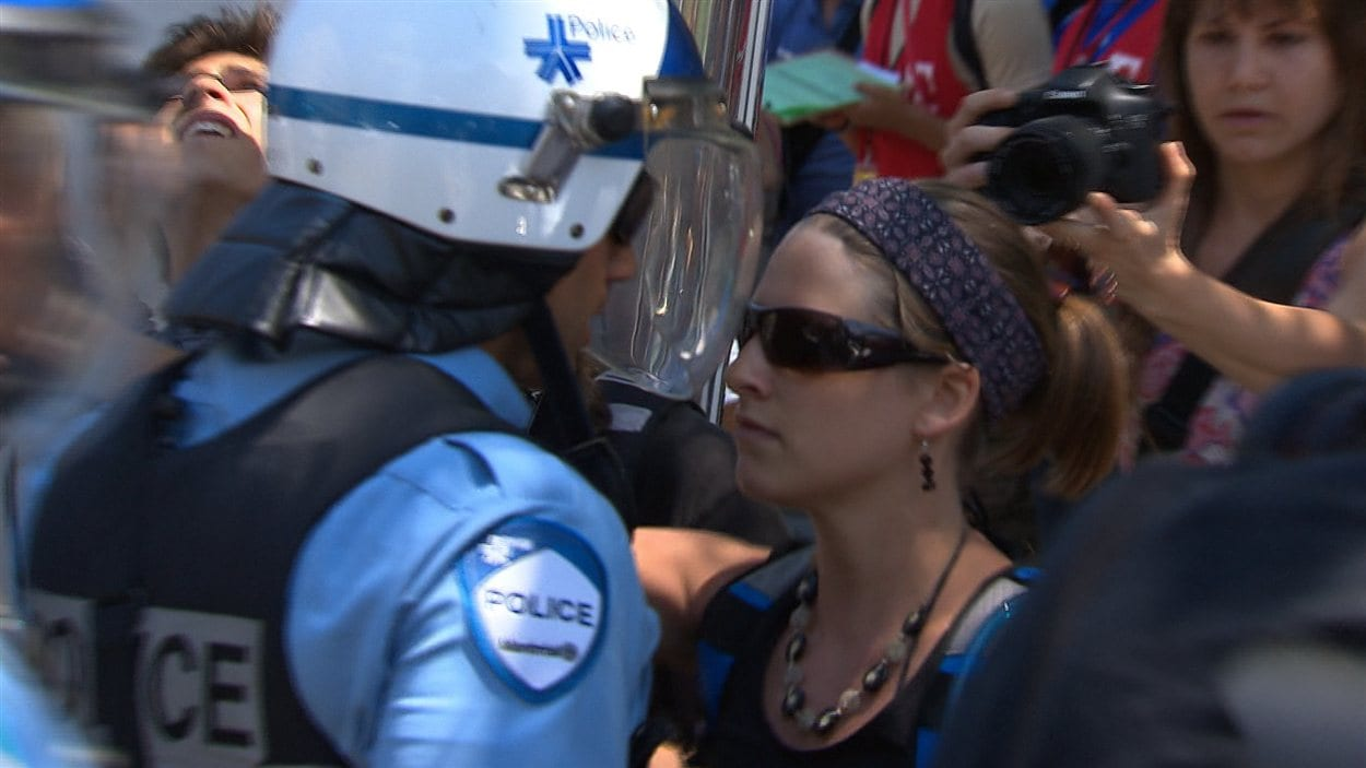 Une manifestante défie un policier du regard, dans le secteur de la rue Crescent.