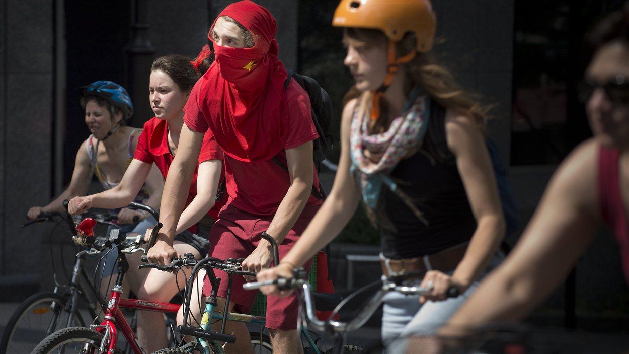 Des personnes contre la hausse des droits de scolarité et le Grand Prix manifestent à vélo, à Montréal.