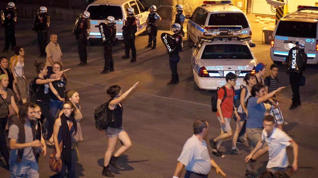À Montréal, des manifestants font le salut hitlérien devant les policiers anti-émeute du SPVM qui surveillent les quartiers généraux de la Sûreté du Québec.