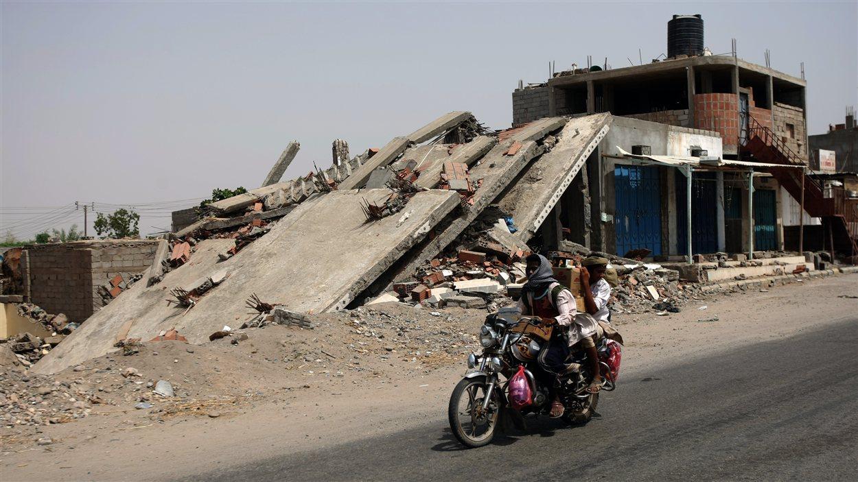 Des hommes circulent à moto devant un bâtiment effondré après l'offensive de l'armée à Jaar.