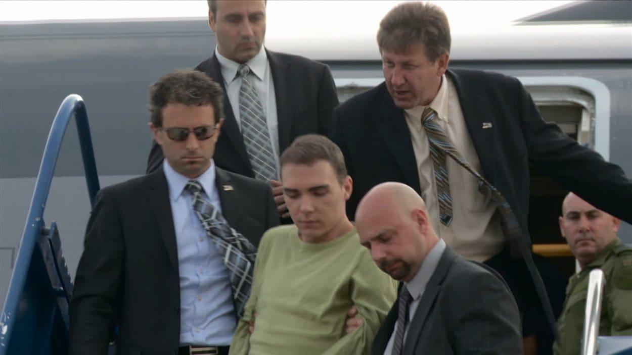 Luka Rocco Magnotta à sa sortie de l'avion, escorté par de nombreux corps policiers.