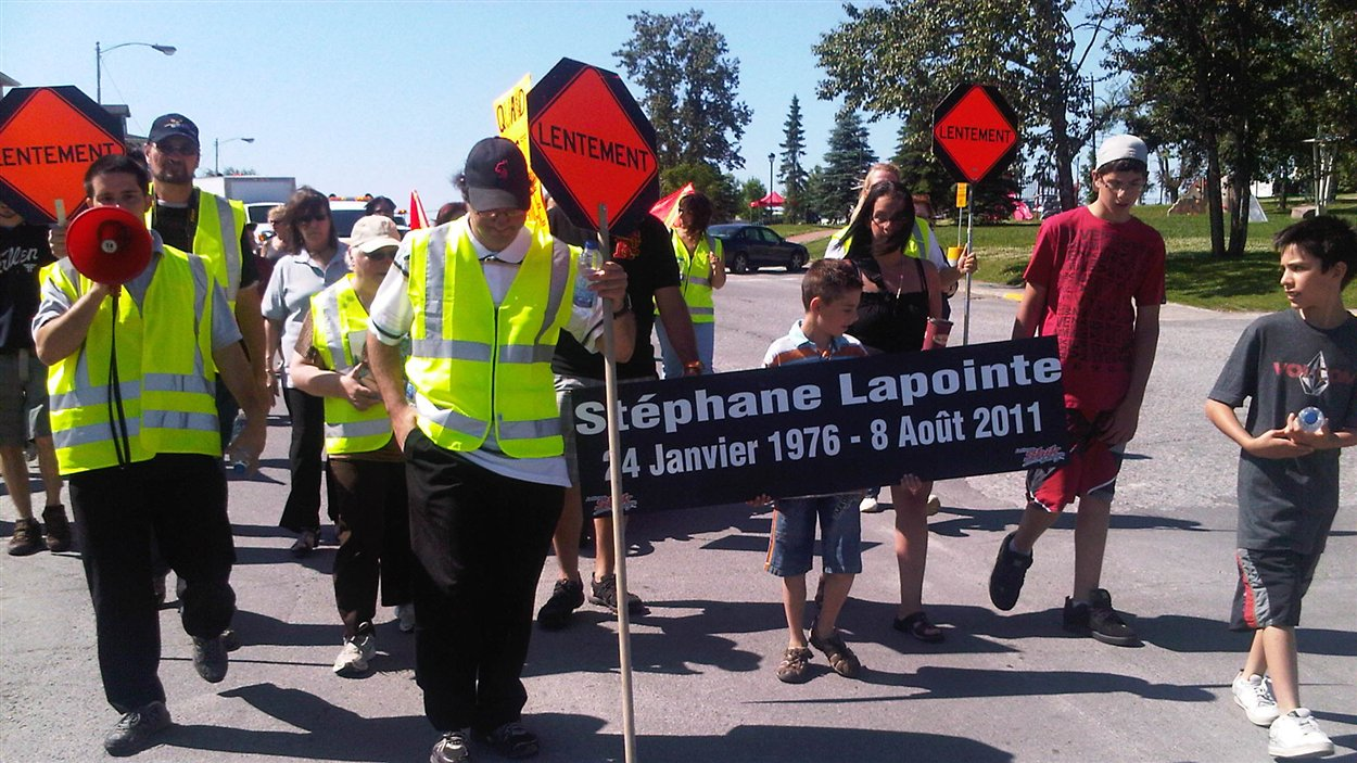 Une cinquantaine de personnes marchent dans les rues d'Amos pour rendre hommage au signaleur routier Stéphane Lapointe, qui a été happé par une voiture en 2011.