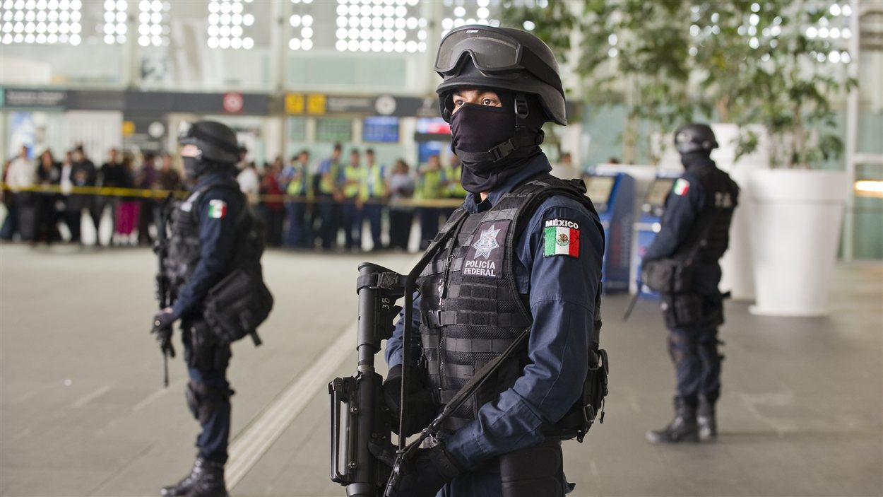 Les policiers fédéraux montent la garde après la fusillade mortelle survenue au terminal 2 de l'aéroport international Benito Juarez de Mexico.