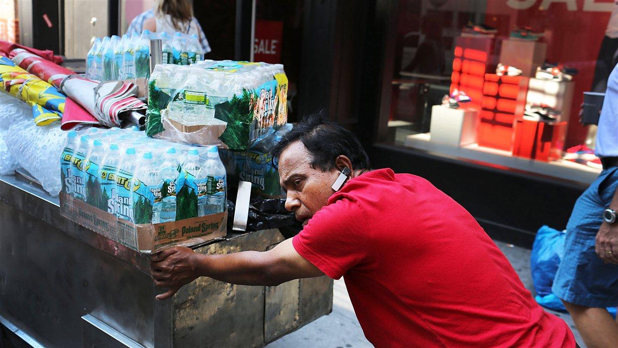 Dans la canicule à New York, un vendeur itinérant pousse son chariot rempli de bouteilles d'eau.