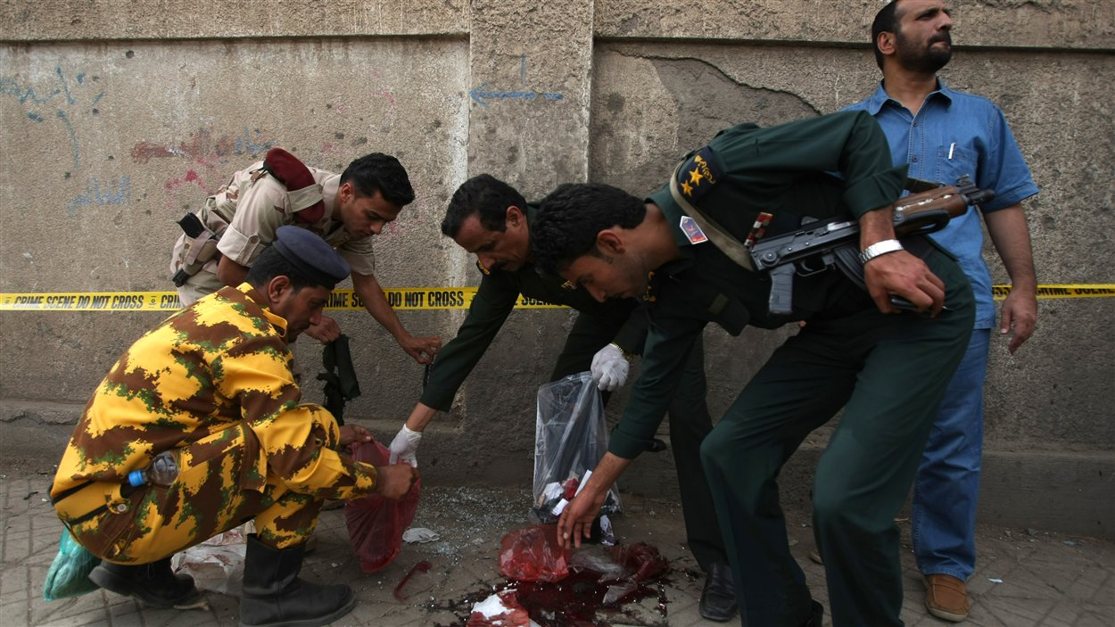 Des policiers et militaires yéménites récoltent des indices sur le lieu d'un attentat suicide, à Sanaa.
